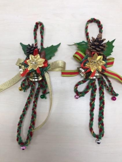 緑色と赤色の毛糸で作ったクリスマスリースの画像。松ぼっくりとリボン、金色の星、色とりどりの鈴で飾り付けられています。
